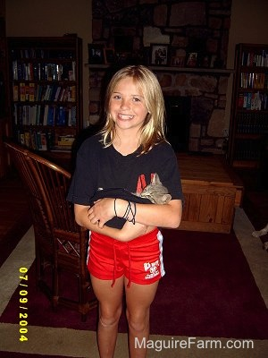 A girl standing inside a living room holding a little gray kitten with a smile on her face. She is wearing red shorts and a black shirt and there are book shelves behind her.