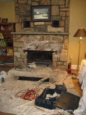The Stone over top of the fireplace opening is being chipped away. There is a drop cloth and tools all over the area.