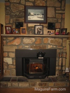 There is a black tea pot on top of the newly inserted wood burning stove. There is a lit fire. The fireplace mantel has family pictures on it. There is a paiting of a farm house in the snow with a blue border above the mantel.