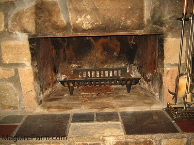 The opening of a fireplace with a wood rack inside of it