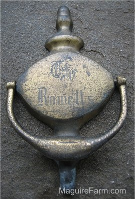 Close Up - A Door Knocker laying on a stone porch. The Words - The Rowell's - are on it