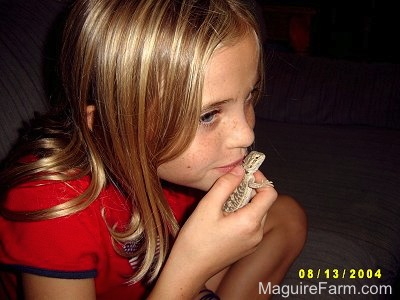 Close Up - A blonde haired girl with a red shirt on is kissing a young bearded dragon