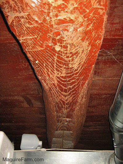 Close up - red colored old basement wooden beam with axe marks in it