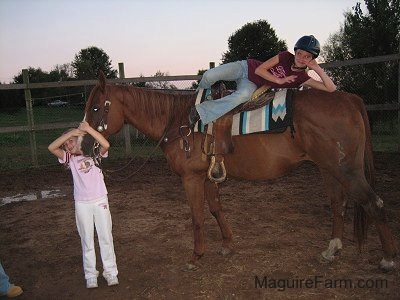 A girl in a burgundy shirt is laying across the top of the back of a brown horse and a second girl in a pink shirt is hugging the horses head.