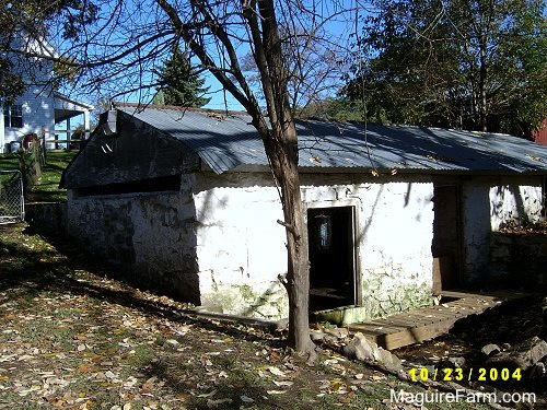 An open window and door of an old stone springhouse. There is a white farm house behind it.