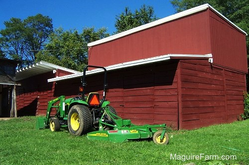 A John Deere 5065E Compact Tractor and Front End Loader with MX-7 cutting deck is parked behind a classic red barn
